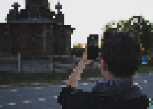 pixelated image of person looking at a wooden building via smartphone